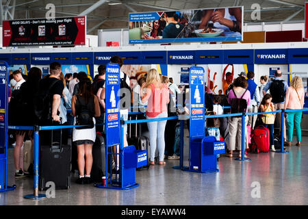 Passengers queue to drop luggage at busy Ryan Air check in desk in Stansted Airport, UK - Stock Photo