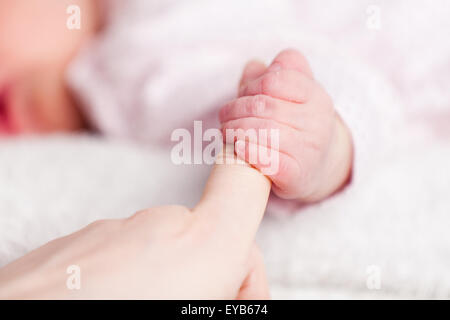 A very young baby gripping her mothers finger showing her tiny nails on her clenched hand. The blurred baby is asleep - Stock Photo