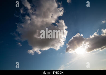 Sun going down behind fluffy clouds - Stock Photo