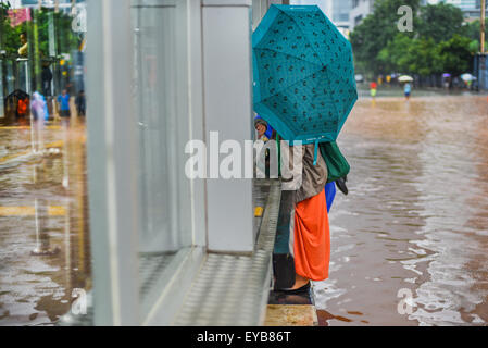 Women tries to avoid floodwater. - Stock Photo