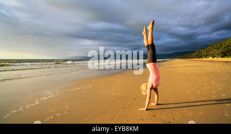 beautiful sporty girl doing handstand yoga asana crane