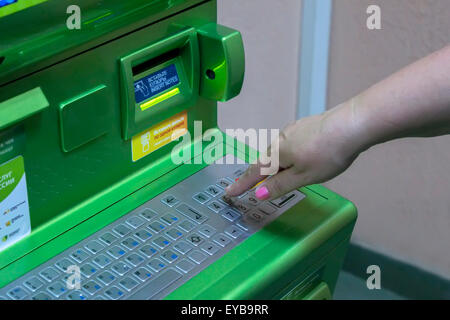 The hand of man (woman) is gaining PIN code on the keypad of the ATM terminal - Stock Photo
