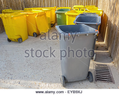 Some garbage containers in gray, yellow and green to recycle - Stock Photo