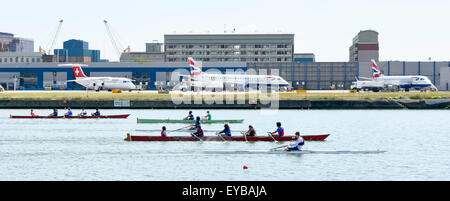 Aircraft at  London City Airport with rowers training in the old Royal Docks next to runway London Docklands Newham - Stock Photo
