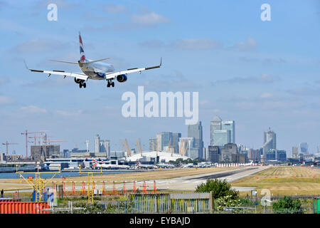 British Airways plane landing London City Airport Newham with O2 arena & Canary Wharf in London Docklands skyline - Stock Photo