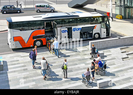 Wheelchair user passengers wait for platform elevator on coach bus adapted for disabled people to travel  ((see - Stock Photo