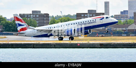 British Airways plane landing at London City Airport BA Cityflyer Embraer 190 G-LCYM burning the rubber tyres upon - Stock Photo