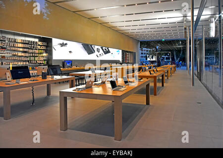 Apple store after closing time with equipment in full view on the classic timber tables in French  modern glass - Stock Photo