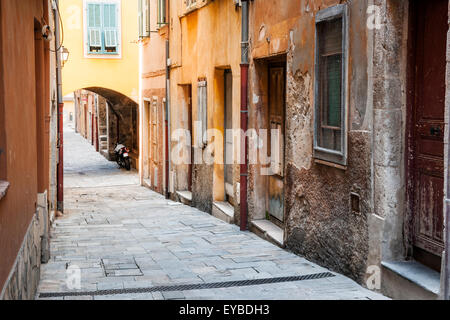 Old houses along narrow cobblestone street in medieval town Villefranche-sur-Mer on French Riviera, France. - Stock Photo