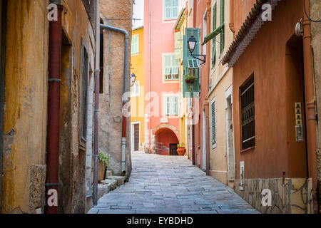 Narrow cobblestone street with bright buildings in medieval town Villefranche-sur-Mer on French Riviera, France. - Stock Photo