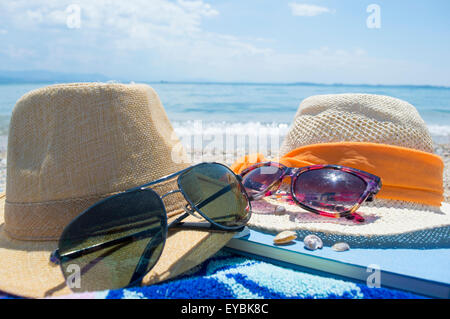 Two straw hats sunglasses and a book on the beach with sea in backgound on a sunny day - Stock Photo