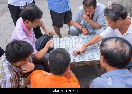 Men playing Chinese chess, Beijing - July 2015 - Stock Photo