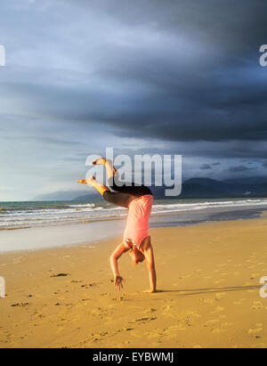 A young woman doing a cartwheel on the beach. - Stock Photo