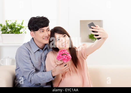 Young man and pregnant woman holding flowers and taking pictures with mobile phone, - Stock Photo