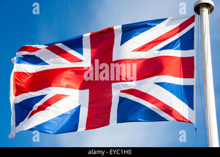 British Union Jack flag flying and fluttering in the wind atop of white flagpole - Stock Photo