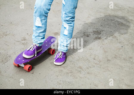 Teenager feet in jeans and gumshoes with skateboard on gray asphalt, selective focus - Stock Photo