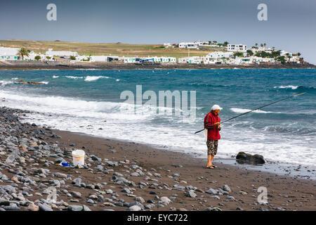 Angler in a stony beach. Playa Quemada, Yaiza. Lanzarote, Canary islands, Spain, Europe. - Stock Photo
