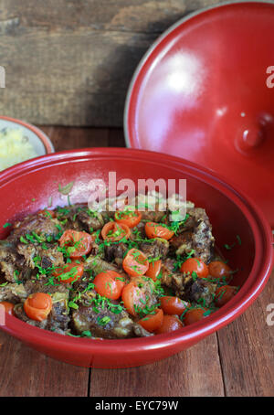 Moroccan tagine with lamb, tomatoes and couscous on a wooden table. Selective focus. - Stock Photo