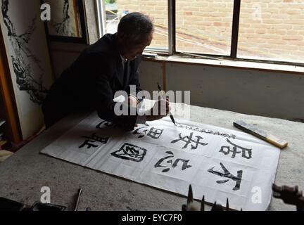 (150727) -- BEIJING, July 27, 2015 (Xinhua) -- Lu Caiwen practises calligraphy at his home in Tengchong, southwest - Stock Photo