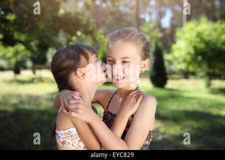 Secrets of childhood - two friends have secrets - Stock Photo