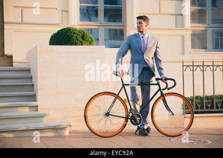 Portrait of a handsome businessman standing outdoors with bicycle and looking away - Stock Photo