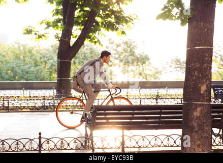 Businessman riding bicycle in park at the morning - Stock Photo