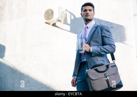 Portrait of a confident businessman standing outdoors near office building - Stock Photo