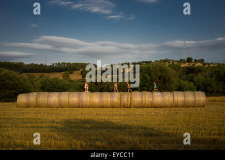 In a field north of Barcelon, Spain, a group of children playing on hay bales. - Stock Photo