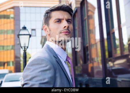 Portrait of a pensive businessman standing outdoors near office building and looking away - Stock Photo