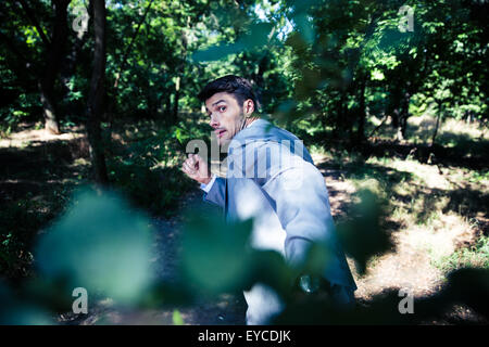 Afraid businessman running away from something outdoors in park - Stock Photo