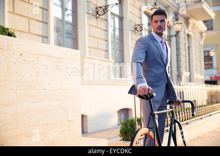 Portrait of a confident businessman standing with bicycle in old town and looking away - Stock Photo