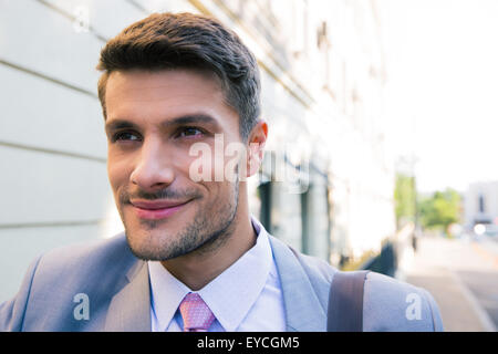Portrait of a happy businessman outdoors looking away - Stock Photo