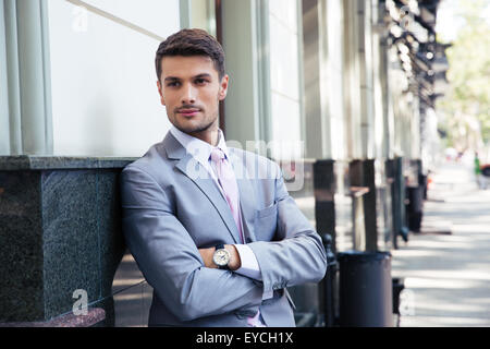 Portrait of a handsome businessman with arms folded standing outdoors in the city - Stock Photo