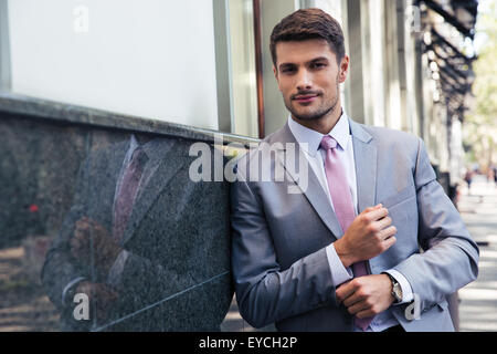 Confident businessman standing outdoors and looking at camera - Stock Photo