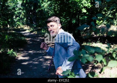 Frightened businessman running away from something outdoors in park - Stock Photo