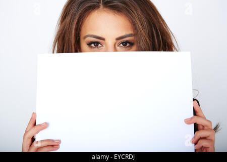 Banner sign woman peeking over edge of blank empty paper - Stock Photo