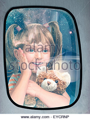 Excited child looking out of window at planets on futuristic space flight - Stock Photo