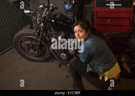 Female mechanic working on motorcycle in workshop - Stock Photo