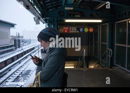 Mid adult woman standing at train station using mobile phone - Stock Photo