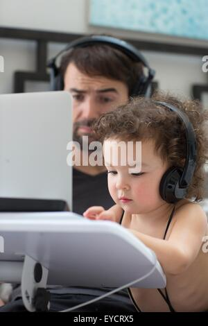 Father watching toddler daughter typing on laptop whilst wearing headphones - Stock Photo