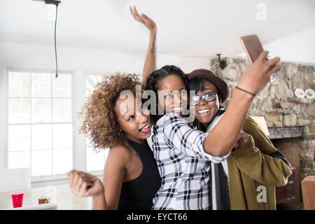 Three young women posing for smartphone selfie in kitchen