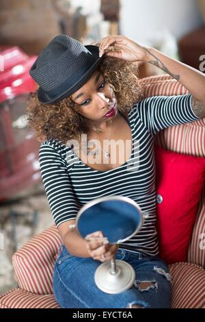 Young woman looking in hand mirror trying on fedora - Stock Photo