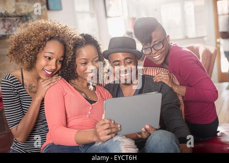 Four adult friends sitting on sofa looking at digital tablet - Stock Photo