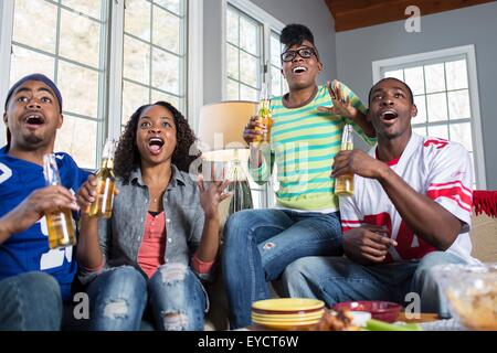 Four adult friends gasping open mouthed whilst watching TV from sofa - Stock Photo