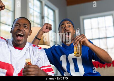 Two male friends celebrating whilst watching TV from sofa - Stock Photo
