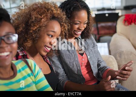 Three female friends reading smartphone texts on living room sofa - Stock Photo
