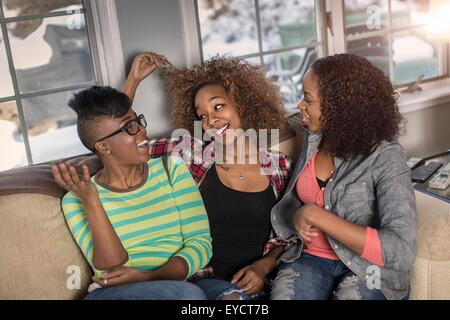 Three female friends chatting on living room sofa - Stock Photo