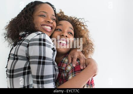 Studio portrait of two young women friends hugging - Stock Photo
