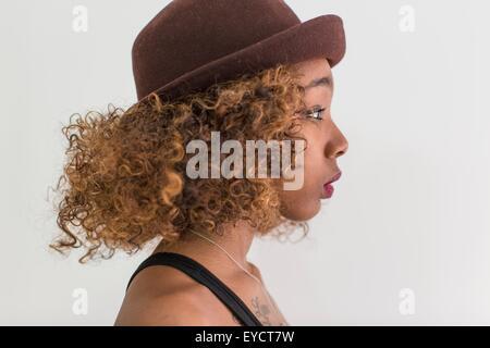 Studio profile portrait of young woman wearing felt hat - Stock Photo
