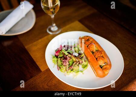 Plate of fried shrimp poboy sandwich on restaurant table - Stock Photo
